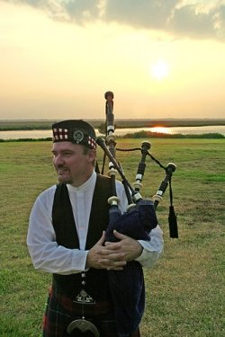 A bagpiper greets the sunset on St. Simons Island. (image from Squiddoo.com)