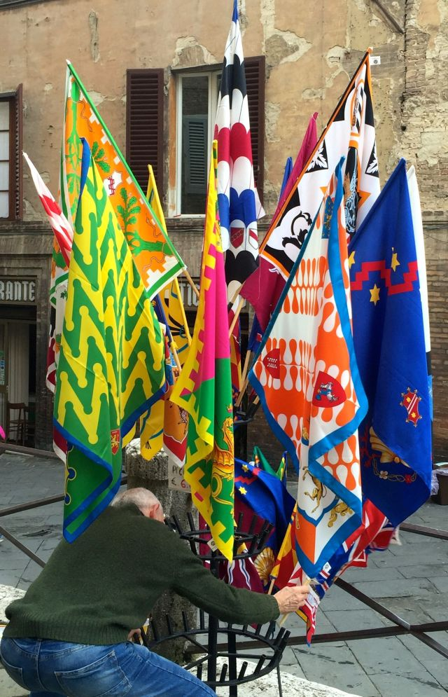 A Sienese vendor readies his display of contrade flags.